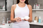 woman standing with open cream