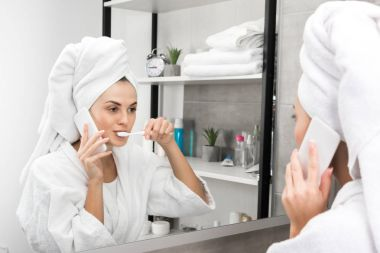 Woman talking by smartphone and brushing teeth