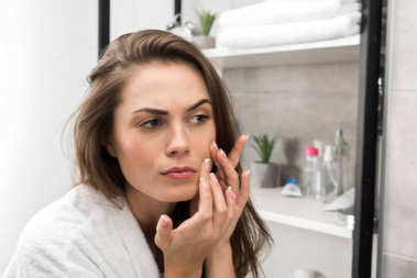 Woman checking face skin