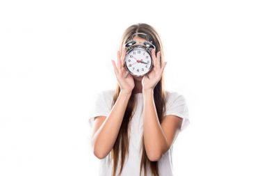 Girl covering face with alarm clock