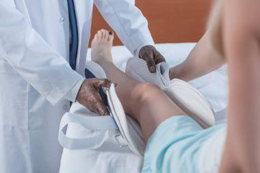 doctor putting on leg brace