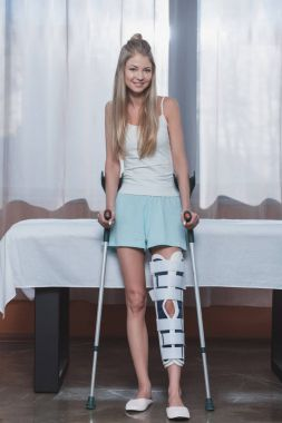girl with crutches and leg brace