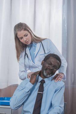 Doctor examining patient neck