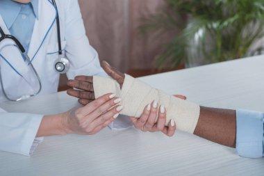 doctor bandaging patient hand