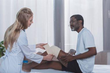 doctor bandaging patient leg