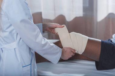 doctor putting on elastic bandage