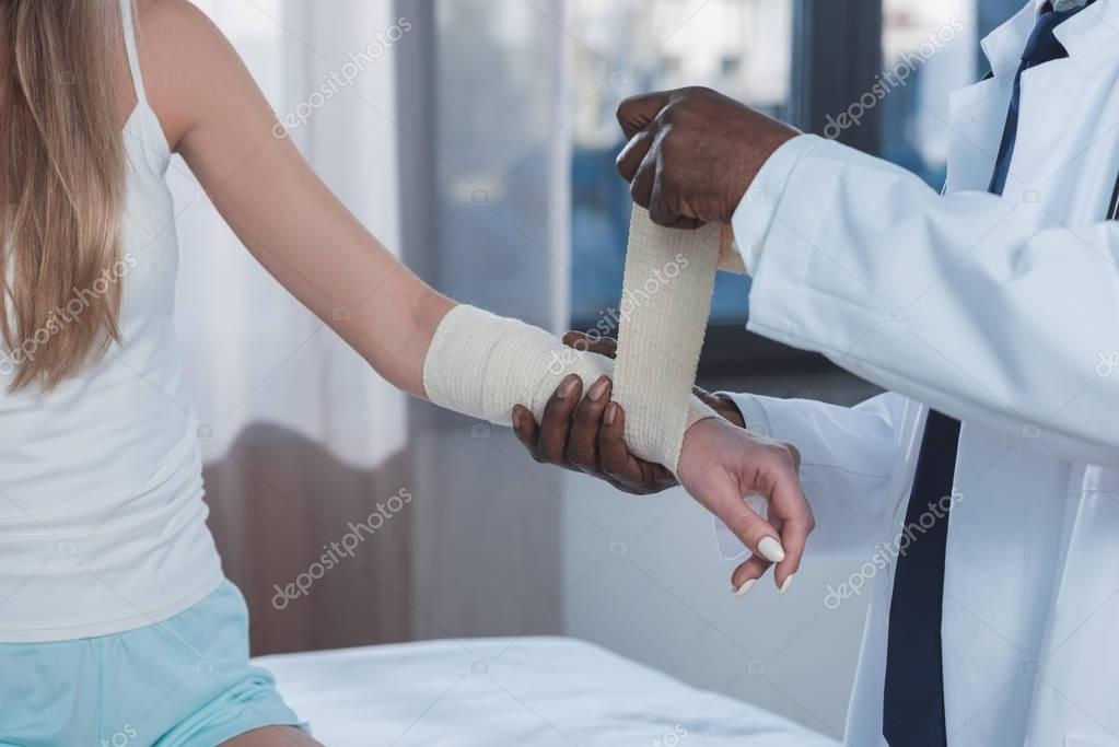 doctor bandaging patient hand