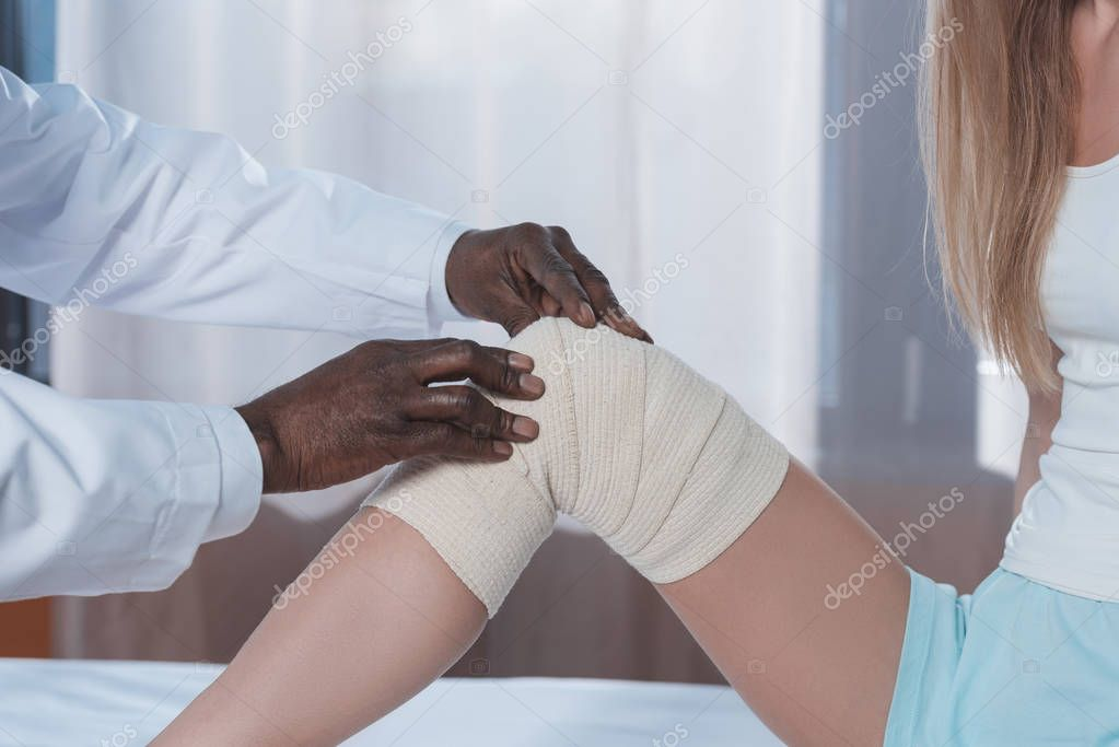 doctor bandaging patient knee