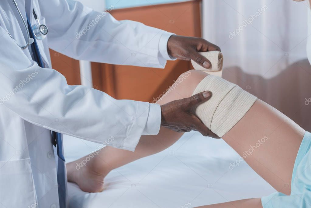 doctor putting on elastic bandage