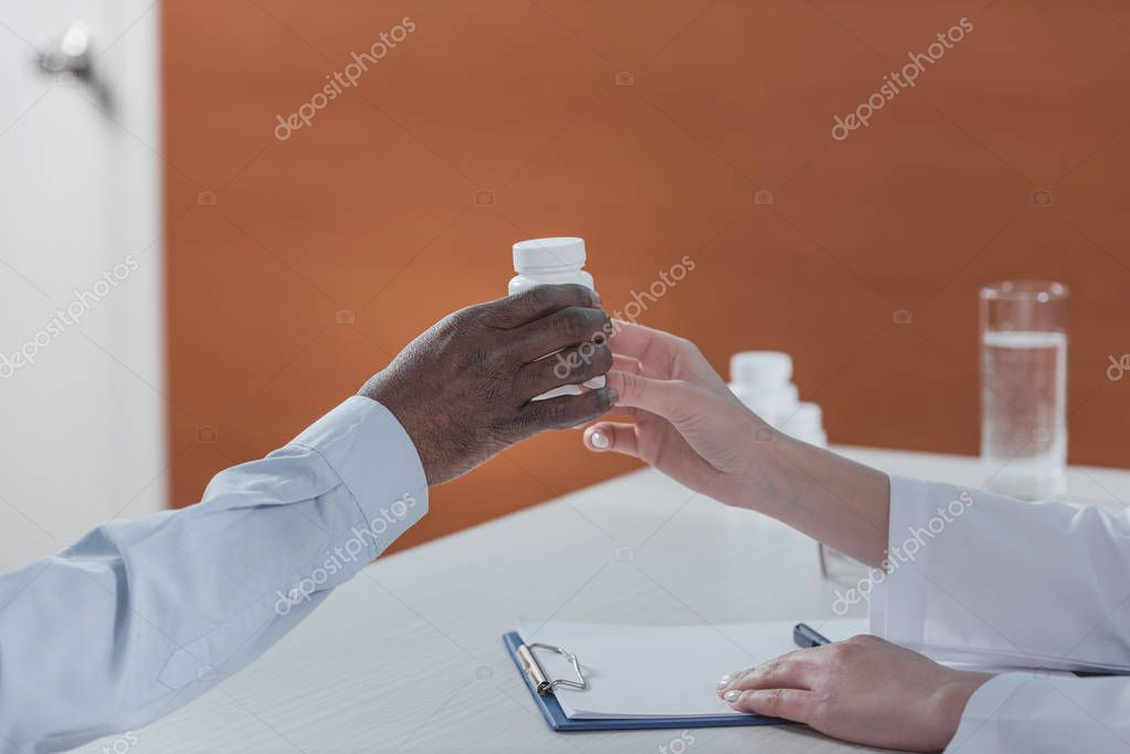 doctor giving plastic jar with pills