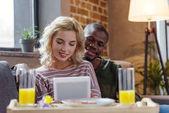 mladý, usměvavý mnohonárodnostní pár společně pomocí tabletu během snídaně doma