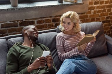 smiling african american man listening music while caucasian girlfriend reading book on sofa at home