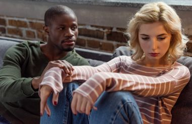 african american man looking at upset girlfriend while sitting on sofa at home, relationship problems concept