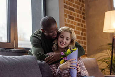 african american man hugging smiling caucasian girlfriend with bouquet of flowers at home