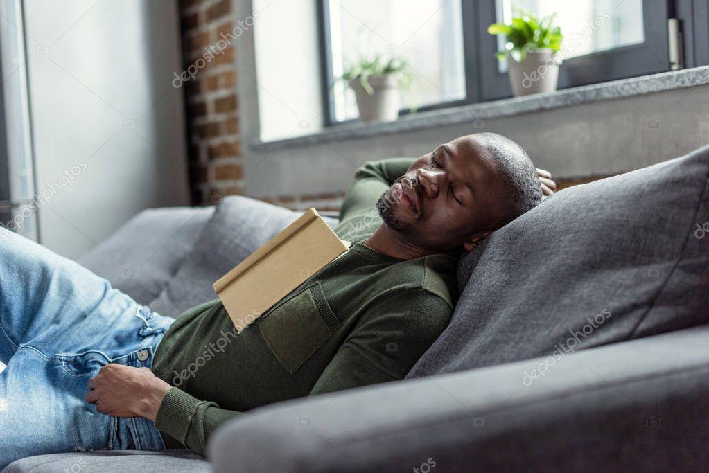 african american man sleeping on sofa