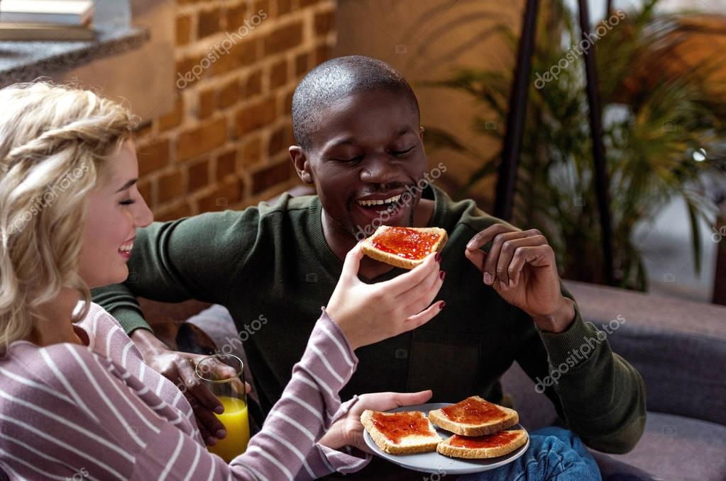 happy woman feeding african american boyfriend with toast during breakfast at home