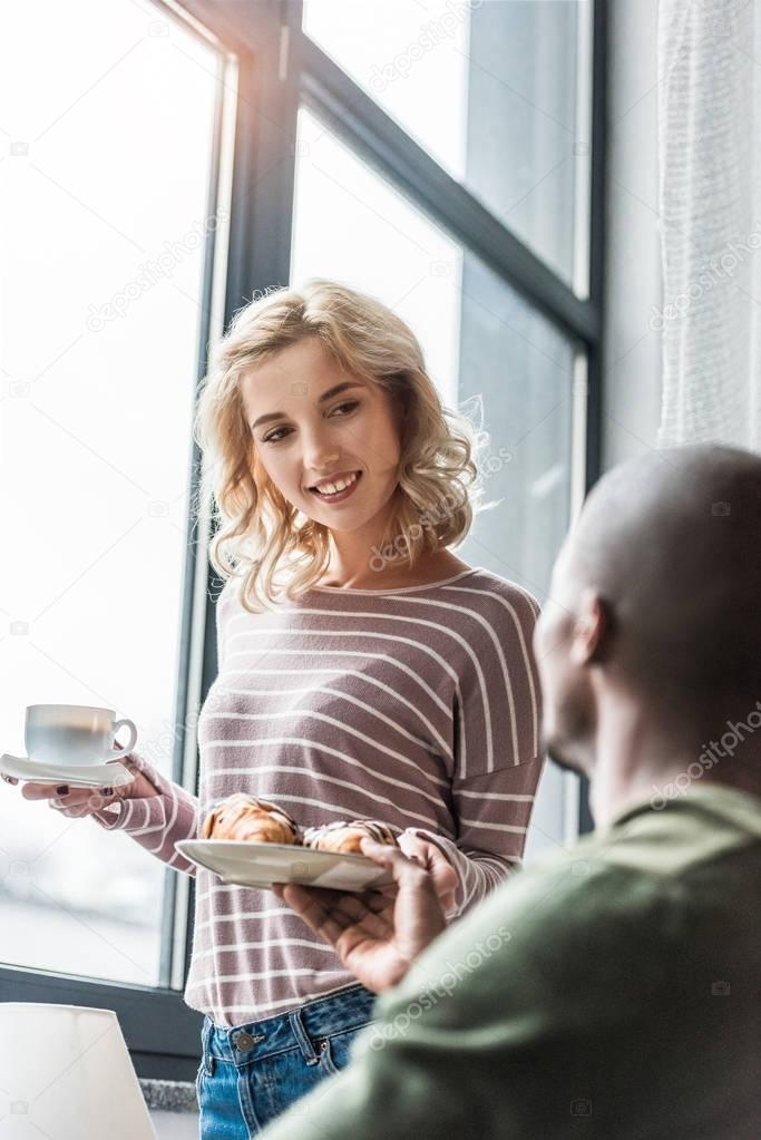 selective focus of smiling woman with breakfast in hands looking at african american boyfriend at home