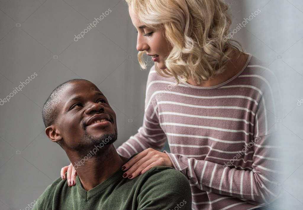 portrait of young multiethnic couple looking at each other at home