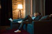 Fényképek a fiatal multikulturális pár tv együtt nézni otthon oldalnézete