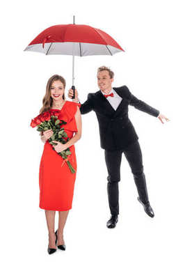 Happy beautiful young woman holding red roses while stylish boyfriend holding umbrella isolated on white stock vector