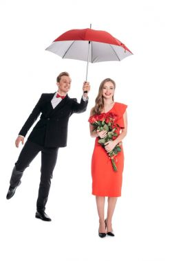 Happy young woman holding red roses while stylish boyfriend holding umbrella isolated on white stock vector
