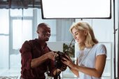 Fotografie portrait of cheerful african american photographer and caucasian model choosing photos together during photoshoot in studio