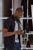 boční pohled na afroamerický fotograf výběru fotografií na fotoaparátu ve studiu