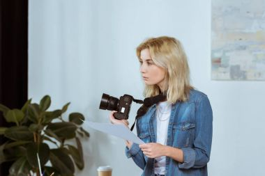 side view of thoughtful photographer with photo camera and photoshoot example looking away in studio