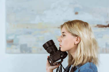 side view of pensive woman with photo camera in hand looking away in studio