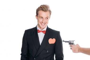 Cropped shot of hand holding revolver and stylish man in suit with heart symbol in pocket smiling isolated on white stock vector