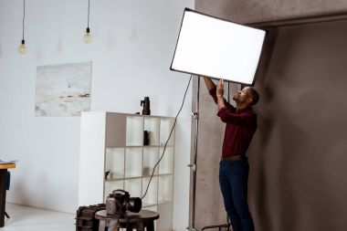 african american photographer getting ready for photoshoot in studio