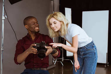 african american photographer and caucasian model choosing photos together during photoshoot in studio