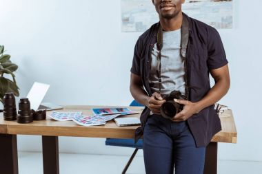 Partial view of african american photographer with photo camera leaning on workplace in office stock vector