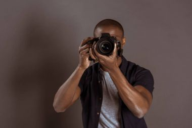 Obscured view of african american photographer taking picture on photo camera stock vector