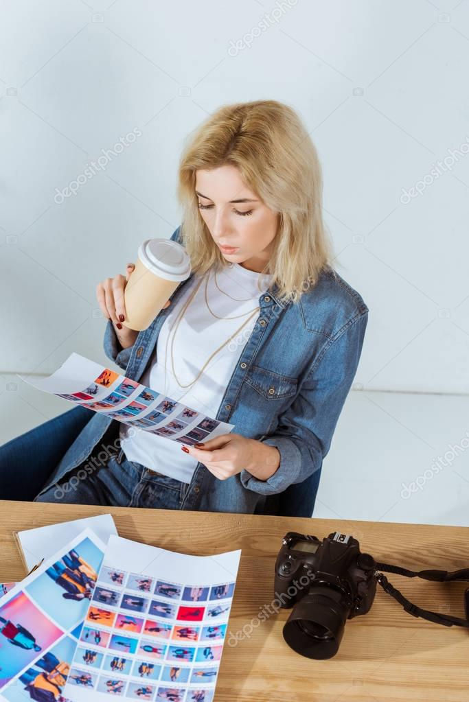 high angle view of photographer with coffee to go looking at photoshoot samples at workplace in office