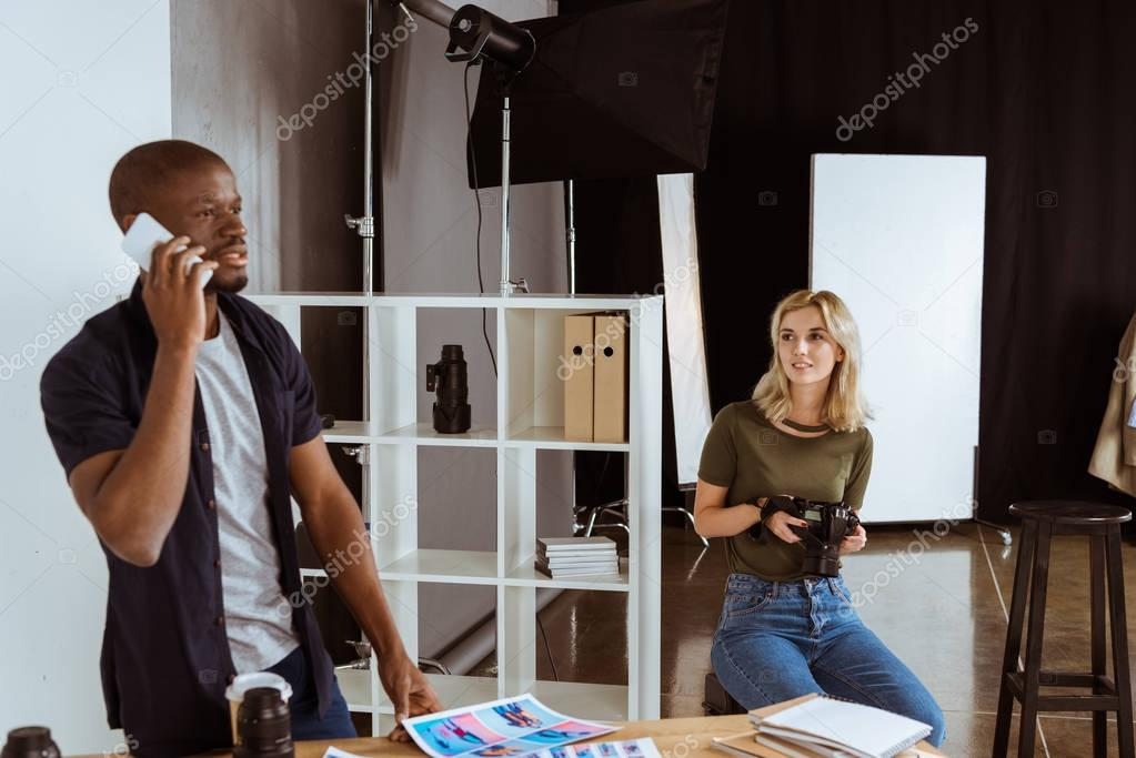 Afican american photographer talking on smartphone while caucaisan colleague choosing photos in studio
