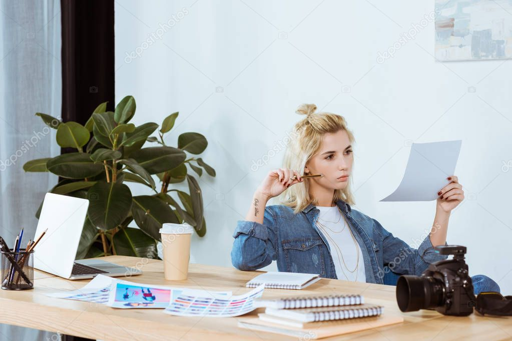 Portrait of thoughtful photographer looking at photoshoot examples at workplace in office