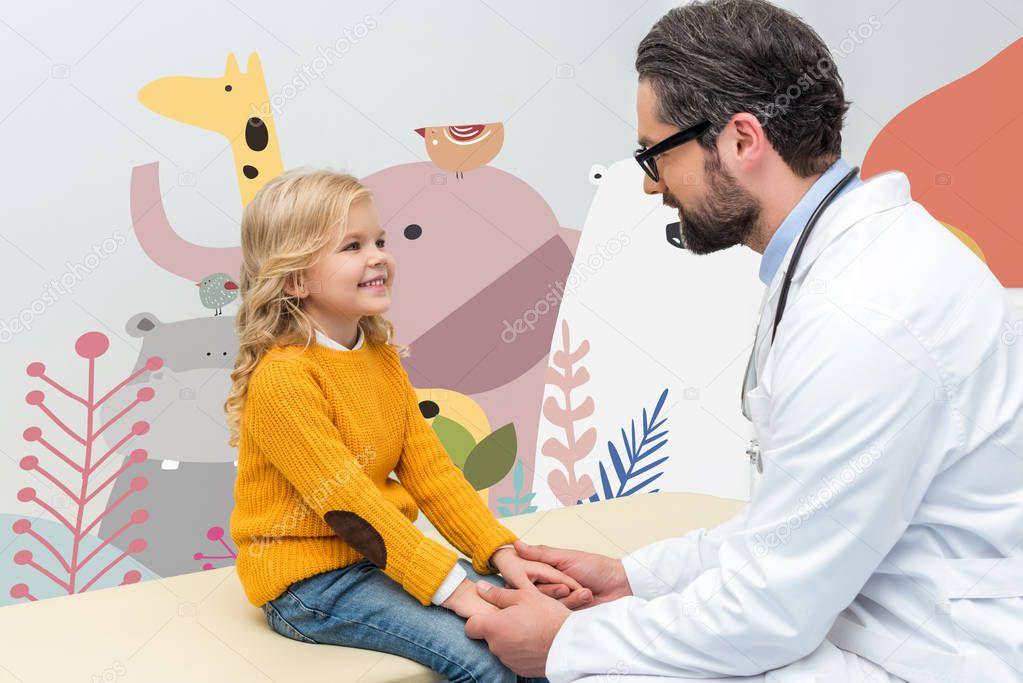 pediatrist holding hands of little girl