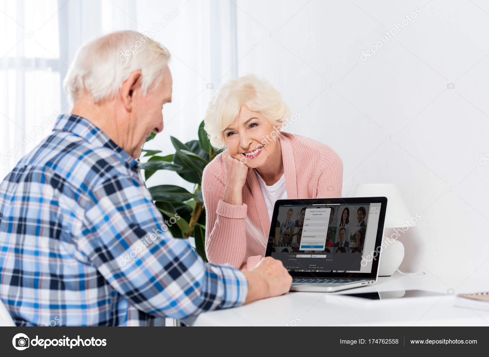 portrait femme senior souriante regardant mari utilisant ordinateur portable maison photo. Black Bedroom Furniture Sets. Home Design Ideas