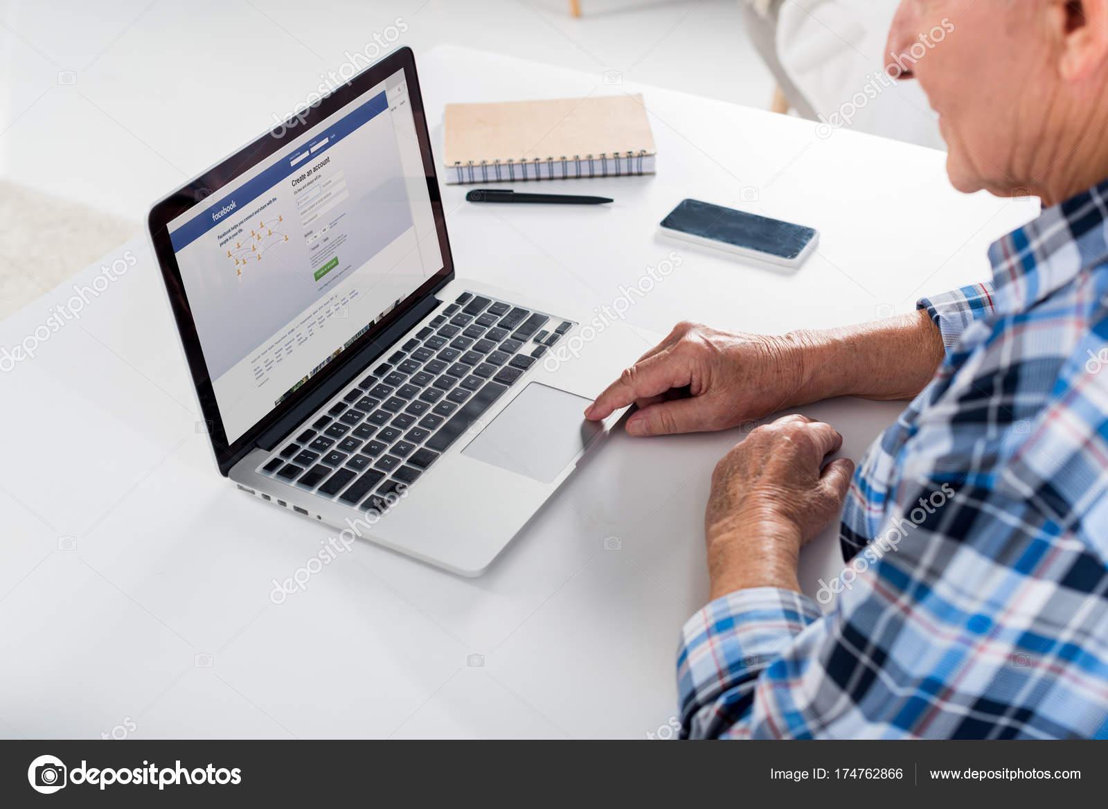 Partial View Senior Man Working Laptop Facebook Logo Table