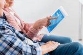 vágott lövés mosolyogva idősebb férfi és nő, digitális tabletta együttes használata