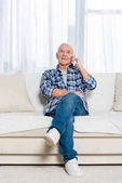 senior man talking on smartphone while sitting on sofa at home