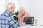 mosolygó vezető nő keresi a férje, amit használ a laptop otthon