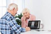 néztem a férjem használ a laptop otthon, mosolygó vezető nő portréja