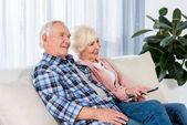 Fotografia Coppie maggiori felici con telecomando, guardare la tv sul divano