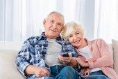 Fényképek idősebb pár kanapén tévénézés távirányítóval