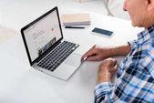 részleges kilátás nyílik a magas rangú ember ül az asztalnál, és használ a laptop airbnb logóval