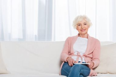 portrait of smiling senior woman with tablet in hands resting on sofa and looking at camera at home