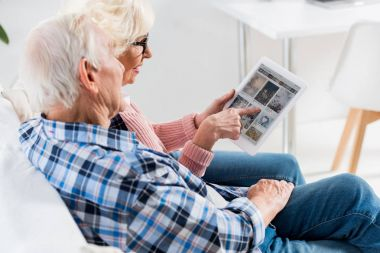 side view of senior couple using digital tablet with pinterest logo together