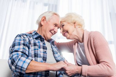 low angle view of happy senior couple looking at each other and holding hands